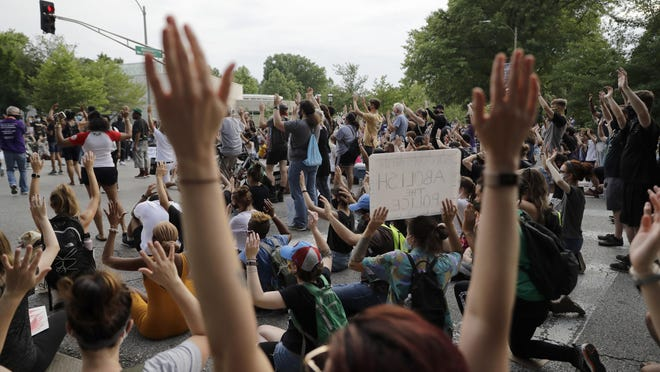 Protesters raise their arms as they block an intersection while bringing attention to racial injustice Friday in St. Louis.