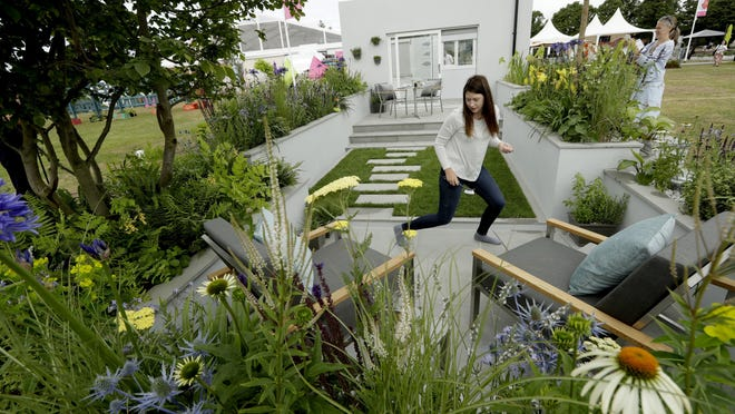 """Rhiannon Williams adjusts final details before her design """"The Urban Rain Garden"""" was judged during the press day for the RHS (Royal Horticultural Society) Hampton Court Palace Flower Show in East Molesey, on the western edge of London, Monday, July 3, 2017."""
