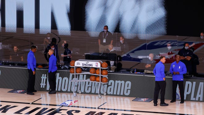 Referees stand on an empty court before the start of a scheduled game between the Milwaukee Bucks and the Orlando Magic for Game 5 of an NBA basketball first-round playoff series, Wednesday, Aug. 26, 2020, in Lake Buena Vista, Fla.