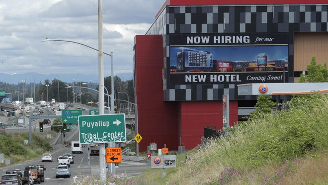 """A large video display reads """"Now hiring for our new hotel coming soon!,"""" Thursday, July 9, 2020, at the new Emerald Queen Casino, which is open, and owned by the Puyallup Tribe of Indians, in Tacoma, Wash. The U.S. economy is stumbling as the viral outbreak intensifies, threatening to slow hiring and deepening the uncertainty for employees, consumers and companies across the country."""
