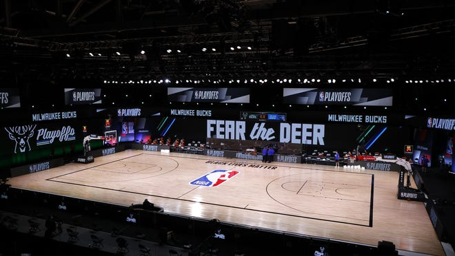 Referees huddle on an empty court at game time of a scheduled game on Tuesday between the Milwaukee Bucks and the Orlando Magic for Game 5 of the Eastern Conference First Round during the 2020 NBA Playoffs at AdventHealth Arena at ESPN Wide World Of Sports Complex in Lake Buena Vista, Florida.