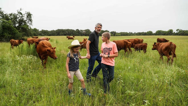 Mark Einkauf with his children Alan, 12, and Caroline, 8, check together the livestock at Einkauf's Blessing Falls Family Farm in Thrall on June 26.