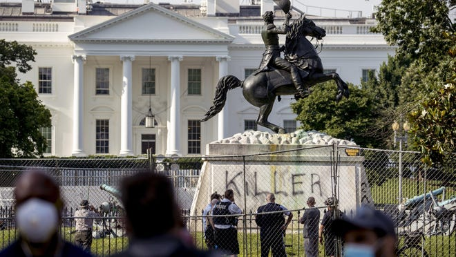 The White House is visible on June 23 behind a vandalized statue of President Andrew Jackson. Protesters had tried to topple the statue of Jackson, who owned slaves and forced the removal of nearly 50,000 Native Americans from their lands during his presidency from 1829-1837.