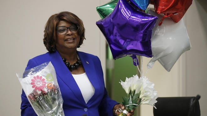 Mayor Ella Jones, right, holds balloons and flowers after being sworn in Tuesday in Ferguson. Jones becomes the first black and first woman to become mayor of Ferguson, the city thrust into the national spotlight after the death of Michael Brown in 2014.