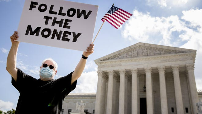 "Bill Christeson holds up a sign that reads ""Follow the Money"" outside the Supreme Court, Thursday, July 9, 2020, in Washington. The Supreme Court ruled Thursday that the Manhattan district attorney can obtain Trump tax returns while not allowing Congress to get Trump tax and financial records, for now, returning the case to lower courts."