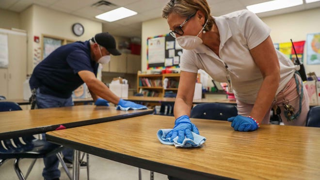 Galindo Elementary School staffer, Berta Perez, right, and Austin school district Facilities Maintenance Service Center technician Isidro Ortega disinfect one of the school's classrooms in March. The Texas Education Agency on Tuesday announced guidelines for returning to classrooms this fall.
