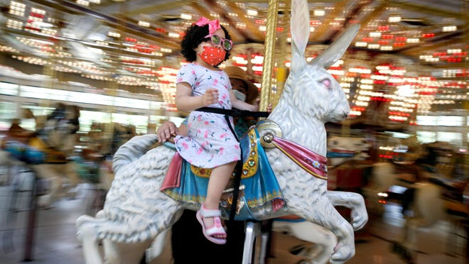Three-year-old Larimar Castro, of New Jersey, chose to sit atop the rabbit for her first carousel ride Sunday afternoon at the Roger Williams Parker Carousel Village, which reopened to the public that day after being closed because of the coronavirus pandemic. She got assistance from  her mom, Larissa Castro.