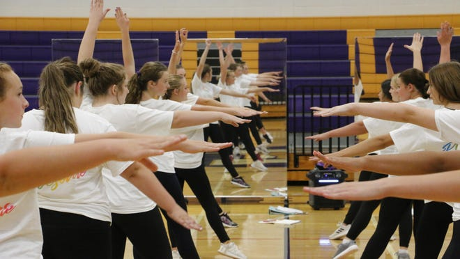 Images of the Early Belles are reflected in mirrors as they practice a dance routine recently in the Early Middle School gym.