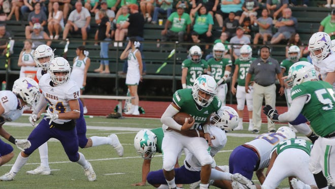 A Bangs Dragon runner is brought down by Early Longhorn defenders in second quarter action Friday night at Dragon Memorial Stadium. Bangs defeated Early 28-0.