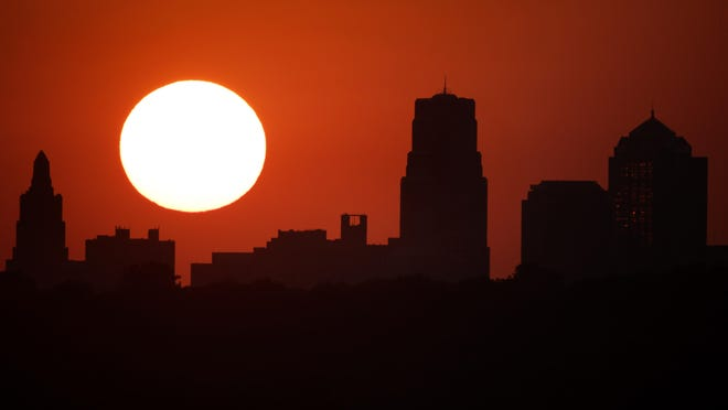 Downtown Kansas City stands against the sky at sunset Wednesday. Kansas City extended its mask order as Columbia paused reopening plans in the wake of a spike in COVID-19 cases across the state.