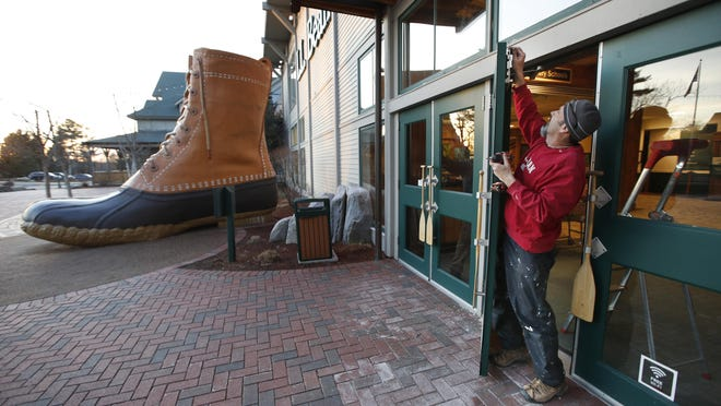 Steve Gauvin installs a lock on a door at the L. L. Bean flagship store, Monday, March 16, 2020, in Freeport, Maine. L. L. Bean closed all its retail stores to prevent the spread of the new coronavirus. The flagship store, which is usually opens 24 hours a day, did not have locks on most of its doors. The store reopened Monday, June 1, 2020.