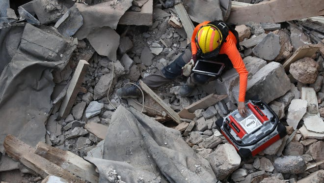 A Chilean rescuer uses a sound tracking machine at the site of a collapsed building in last month's massive explosion after getting signals there may be a survivor under the rubble in Beirut, Lebanon, Early Friday, Sept. 4, 2020. A pulsing signal was detected Thursday from under the rubble of a Beirut building that collapsed during the horrific port explosion in the Lebanese capital last month, raising hopes there may be a survivor still buried there.