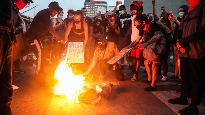 Protesters burn the American flag in front of Austin police headquarters during a march Friday against racial injustice.