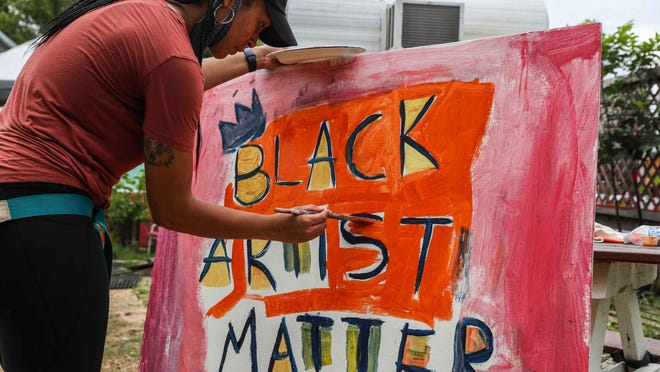 "Melissa Adams paints ""Black Artists Matter"" on a canvas at Kenny Dorham's Backyard next to the new mural with the same phrase near the intersection of 11th and Waller streets in East Austin on Thursday."