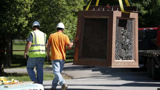 Workers on Tuesday remove the pedestal that supported a statue of Christopher Columbus in St. Louis in Tower Grove Park. St. Louis County is now considering whether to rename roads and other public facilities that honor known racists.