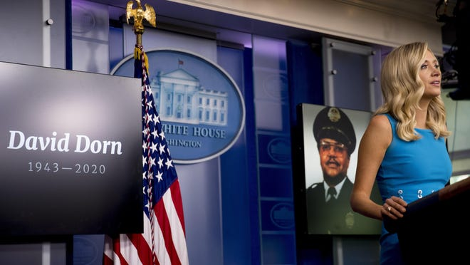 A photograph of retired St. Louis police captain David Dorn, who was shot and killed while guarding a pawn shop from a looter in June 2020, is displayed behind White House press secretary Kayleigh McEnany as she speaks during a briefing at the White House in Washington.