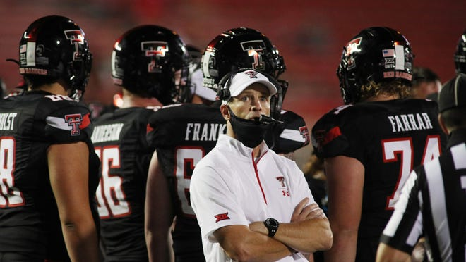 Texas Tech coach Matt Wells checks the scoreboard during his team's 35-33 victory Saturday night against Houston Baptist. The Red Raiders had more than a dozen players who would have suited up under normal circumstances not available for the season opener at Jones AT&T Stadium.