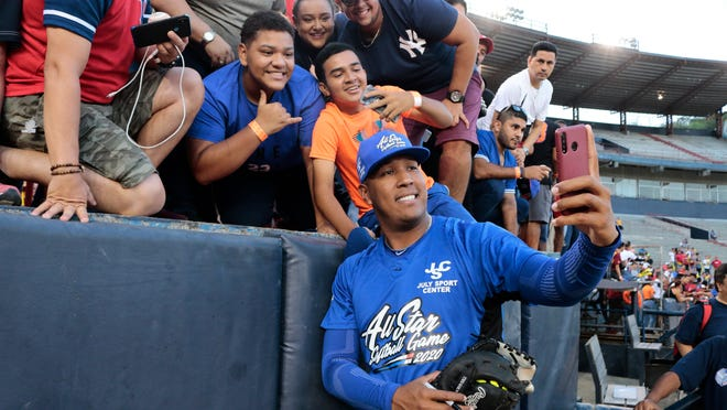"In this Jan. 11, 2020, file photo, Kansas City Royals' Salvador Perez takes a photograph with a fan's cellphone prior to an All-Star exhibition softball game at Rod Carew stadium in Panama City, Panama. When the virus wanes enough to allow the games to begin again, the very essence of these events will likely be missing. ""You know how much I love to talk to the fans, you know? To be in conversation, to throw the ball to kids,"" Kansas City Royals catcher Salvador Perez said."