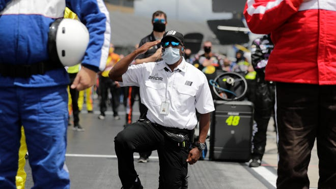 A NASCAR official kneels during the national anthem before Sunday's race at Atlanta Motor Speedway.