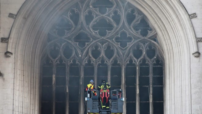 A French firefighting brigade work to extinguish the blaze at the Gothic St. Peter and St. Paul Cathedral, in Nantes, western France, Saturday. The fire shattered stained glass windows and sending black smoke spewing from between its two towers of the 15th century, which also suffered a serious fire in 1972.