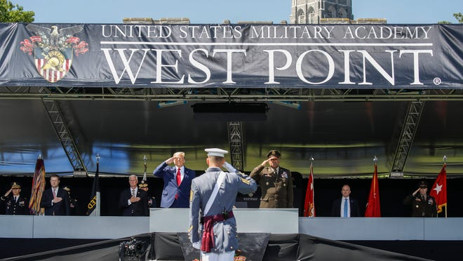 President Donald Trump, left, and United States Military Academy superintendent Darryl A. Williams, right, salute alongside graduating cadets as the national anthem is played during commencement ceremonies Saturday in West Point, N.Y.