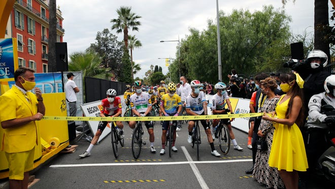 Riders wear face masks as they wait for the start of the first stage of the Tour de France in Nice.