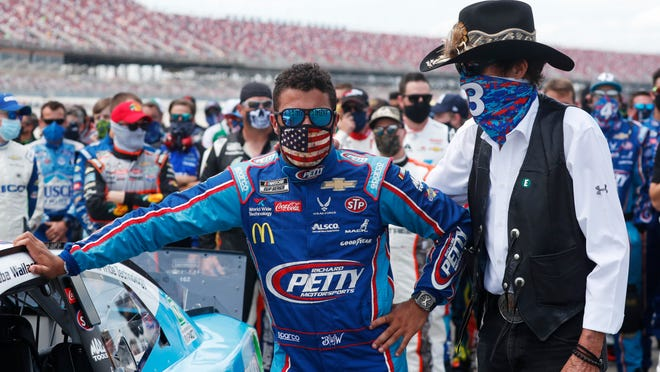 "Bubba Wallace, shown with team owner Richard Petty, said the decision to race this weekend should not be interpreted as ""turning away from the dark and evil acts that have taken over our nation."""