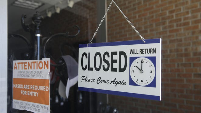 FILE - This July 18, 2020 file photo shows a closed sign in the window of a barber shop in Burbank, Calif. California's unemployment rate has fallen to 11.4% in August. The Employment Development Department says the state added 101,900 jobs in August. Most of those were government jobs, including temporary positions for the U.S. Census. California lost more than 2.6 million jobs in March and April because of the coronavirus.