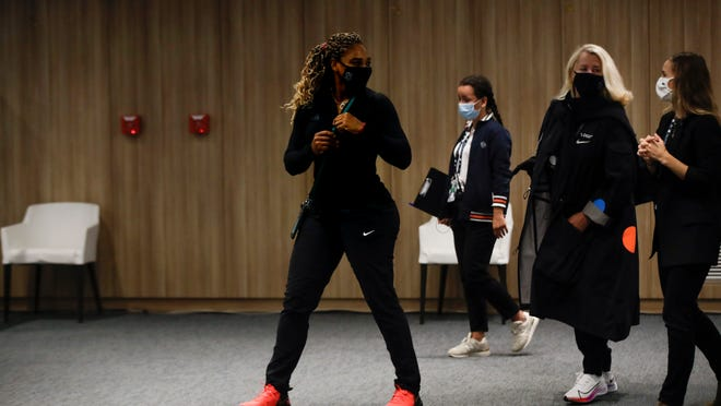 Serena Williams of the U.S., center, leaves after a video link press conference in which she announced her withdrawal from the tournament because of an Achilles injury prior to her second round match of the French Open tennis tournament at the Roland Garros stadium in Paris, France, Wednesday, Sept. 30, 2020.