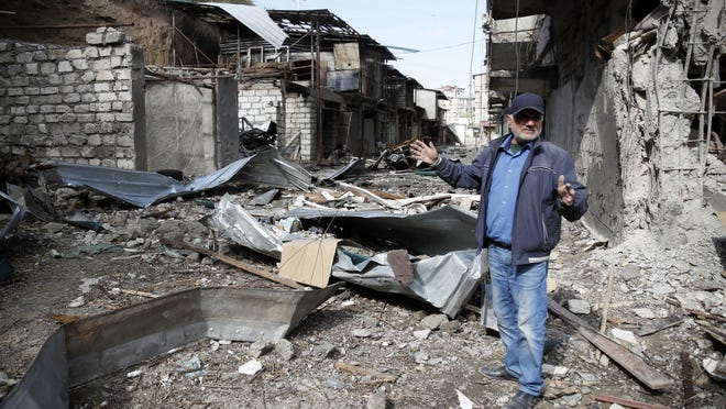 Eduard Chechyan gestures in the yard of his apartment building destroyed by shelling by Azerbaijan's artillery during a military conflict in Stepanakert, the separatist region of Nagorno-Karabakh, Saturday..