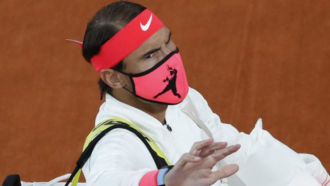 Spain's Rafael Nadal wears a face mask as he walks onto the court for the final match of the French Open tennis tournament against Serbia's Novak Djokovic at the Roland Garros stadium in Paris, France, Sunday, Oct. 11, 2020.