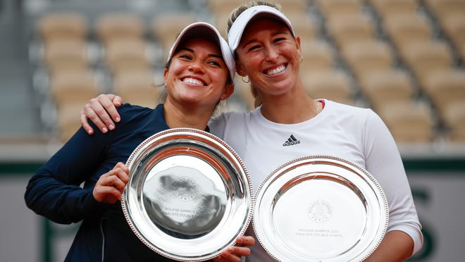 Chile's Alexa Guarachi, right, and Desirae Krawczyk of the U.S. hold the runner-up trophy after losing the women's doubles final match of the French Open tennis tournament against Hungary's Timea Babos and France's Kristina Mladenovic at the Roland Garros stadium in Paris, France, Sunday, Oct. 11, 2020. (AP Photo/Alessandra Tarantino)