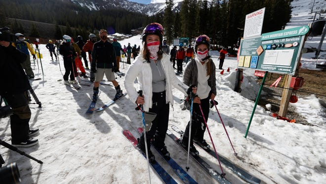 Skiers wear face coverings as they wait to board a lift at the reopening of Arapahoe Basin Ski Resort, which closed in mid-March to help in the effort to stop the spread of the new coronavirus in Keystone, Colo. Winter sports enthusiasts will encounter restrictions at resorts in the season ahead to accommodate COVID rules.