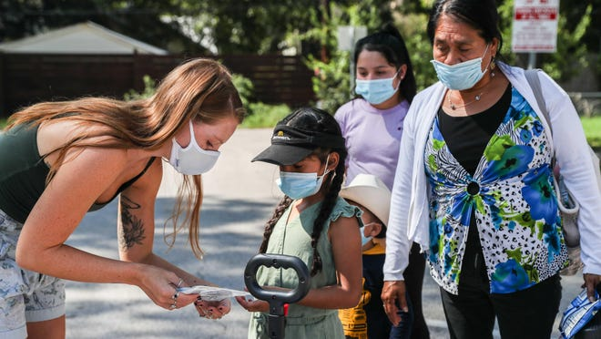 Volunteer Maggie Becker hands a masks to Jackie Torres during the HALO Life initiative providing high quality masks to people in need on Sept. 12.