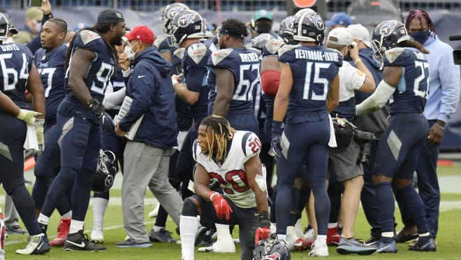 Houston Texans strong safety Justin Reid kneels on the field as Tennessee Titans players celebrate after the Titans won 42-36 in overtime Sunday. On Monday, interim coach Romeo Crennel took the blame for the loss.