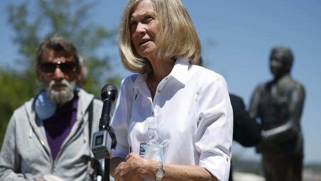 Janet Johnson of Pawcatuck, Ct., front, speaks at a news conference while her husband, Norman, looks on after the sentencing hearing Wednesday, July 1, 2020, for James Curtis Clanton in the death of Helene Pruszynski, Janet Johnson's younger sister, four decades ago in Castle Rock, Colo. Clanton has been sentenced to life in prison.