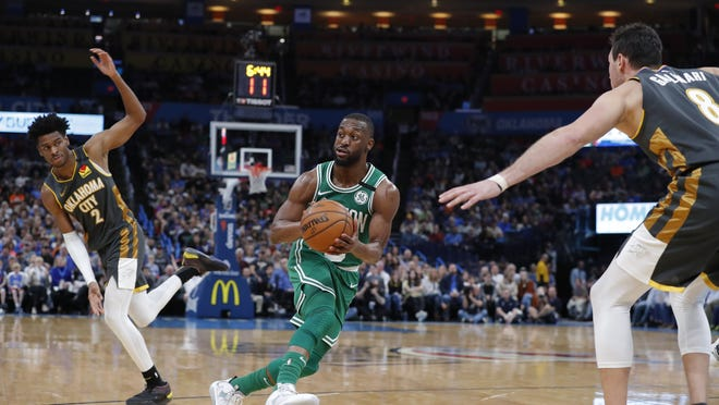 Boston Celtics guard Kemba Walker (8) drives to the basket between Oklahoma City Thunder guard Shai Gilgeous-Alexander (2) and forward Danilo Gallinari (8) during the second half at Chesapeake Energy Arena on Feb. 9, 2020.