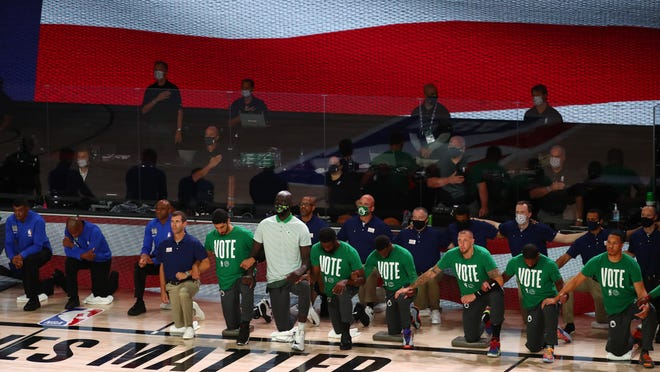 Members of the Boston Celtics kneel during the playing of the national anthem before Game 4 of the Eastern Conference Finals of the 2020 NBA Playoffs against the Miami Heat at AdventHealth Arena on Sept. 23, 2020.