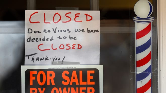 FILE - A For Sale By Owner and closed due virus sign is displayed in the window of Images On Mack in Grosse Pointe Woods, Mich., Thursday, April 2, 2020.