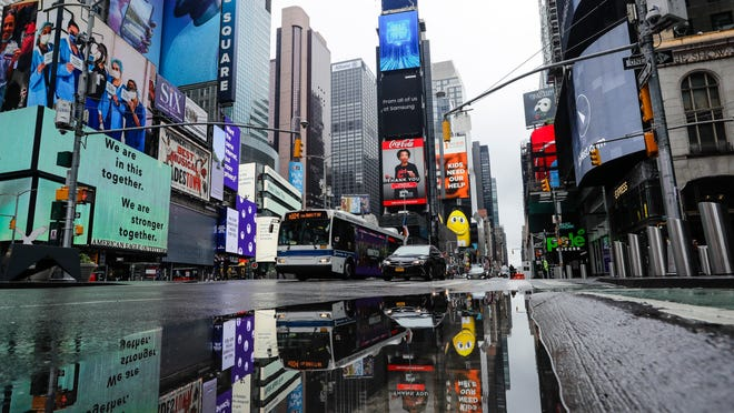 Vehicles move through a nearly empty Times Square during the coronavirus pandemic, Saturday, May 23, 2020, in New York.