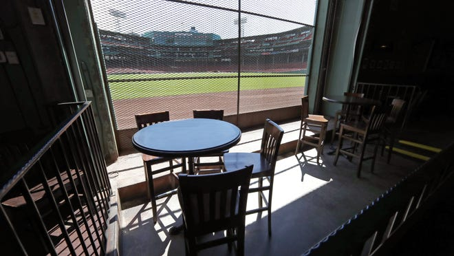 This June 25, 2020, photo shows the view of the baseball field at Fenway Park from the Bleacher Bar in Boston. Located inside the outfield structure at Fenway, it might be one of the few places where fans can watch live MLB baseball this year. Like the Knothole Gangs of the sport's early days, fans hoping to catch a glimpse of a ballgame in person this season will be pressing their faces up against hotel windows, peering through metal grates or clambering up to rooftops when baseball returns this month in otherwise empty stadiums.