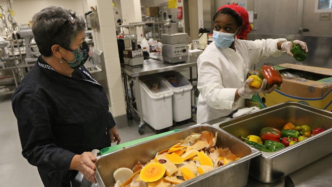 With ingredients partially donated by Food Link, students in the Culinary Arts Career Major at Minuteman High School prepared meals, Nov. 5, 2020. The meals will then be given back to Food Link, which will distribute them to various non-profits. Chef Instructor Anita Currier consulted with junior Carine Valery, 16, from Belmont, about the vegetables she was preparing for Vegetable Lasagna.
