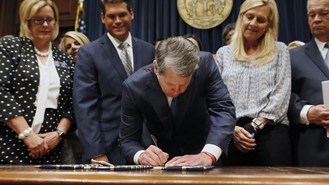FILE - Georgia's Republican Gov. Brian Kemp, center, signs legislation Tuesday, May 7, 2019, in Atlanta, banning abortions once a fetal heartbeat can be detected.