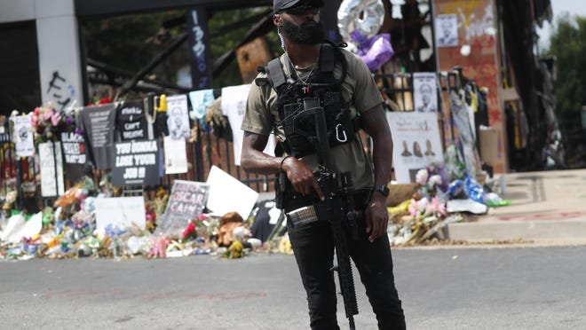 An armed protester awaits the casket of Rayshard Brooks to pass by the area where he was killed near a Wendy's restaurant on Tuesday, June 23, 2020, in Atlanta.