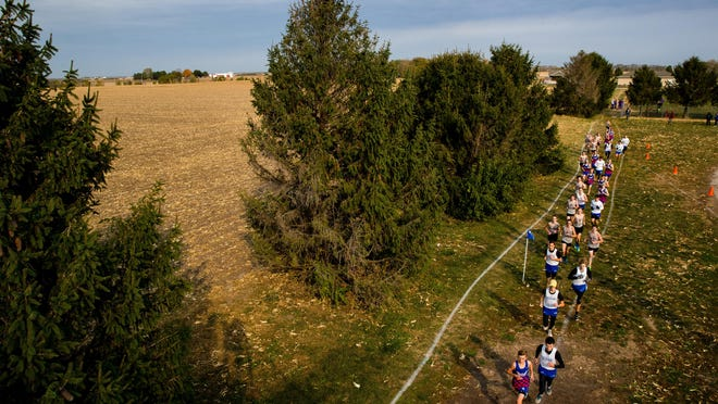 Boys competing in the final Sangamo Conference cross country meet run alongside the perimeter of the Auburn High School football field Saturday. The course location was chosen and configured to maximize space for fans to social distance during the race.