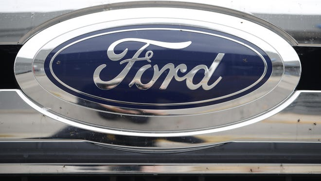In this Sunday, Oct. 20, 2019, photograph, the company logo shines off the grille of an unsold 2019 F-250 pickup truck at a Ford dealership in Littleton, Colo.