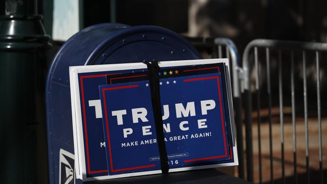 Trump signs sit beside a mailbox as supporters of President Donald Trump set up to protest outside the Pennsylvania Convention Center, where vote counting continues, in Philadelphia, Monday, Nov. 9, 2020, two days after the 2020 election was called for Democrat Joe Biden.