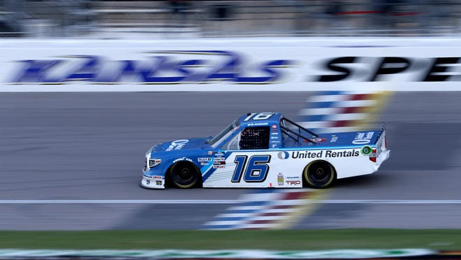 Austin Hill, driver of the No. 16 United Rentals Toyota, crosses the finish line to win the NASCAR Gander RV & Outdoors Truck Series race at Kansas Speedway Friday night.