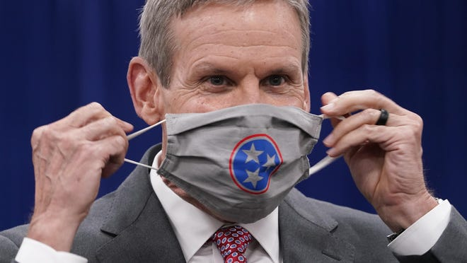 Tennessee Gov. Bill Lee puts on his mask during a break in the state budget hearings Nov. 10 in Nashville. Lee has opposed a statewide mask mandate, stressing personal responsibility.