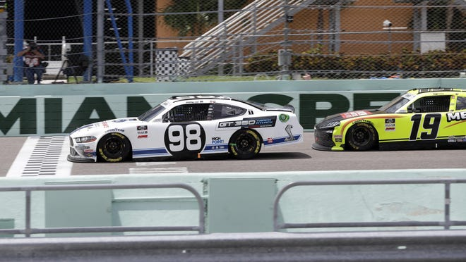 Chase Briscoe (98) crosses the finish line ahead of Brandon Jones (19) to win a NASCAR Xfinity Series race Sunday, June 14, in Homestead, Fla.
